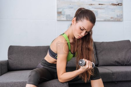 selective focus of serious sportswoman sitting on couch and exercising with dumbbell at home