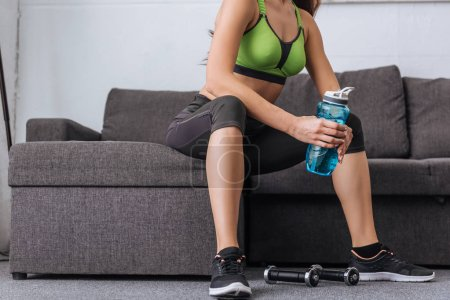 Photo for Partial view of sportswoman with sport bottle sitting on couch at home - Royalty Free Image