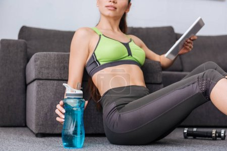 Photo for Sportswoman with water bottle using digital tablet at home - Royalty Free Image