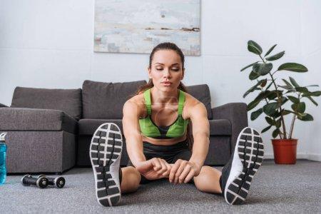 Photo pour Sportive assis et la pratique qui s'étend d'exercice à la maison - image libre de droit
