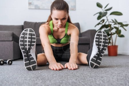 selective focus of sportswoman sitting and doing stretching exercise at home