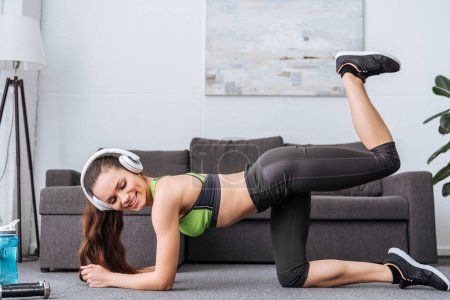 smiling sportswoman in headphones doing donkey kick exercise at home