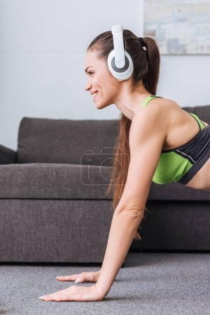 beautiful smiling sportswoman in headphones doing plank exercise at home