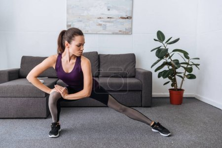 Photo for Beautiful concentrated sportswoman doing lunges at home - Royalty Free Image