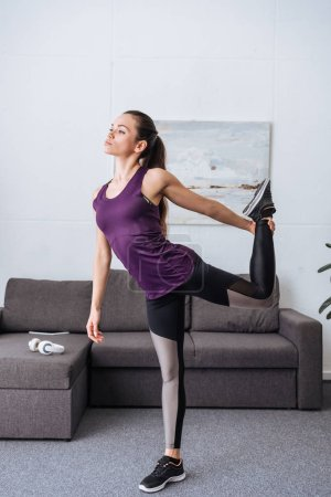 beautiful young sportswoman stretching before workout at home