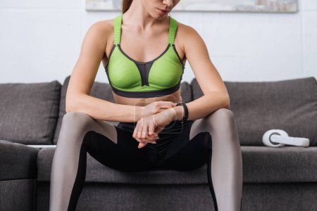Photo for Cropped view of sportswoman sitting on couch and looking at watch at home - Royalty Free Image