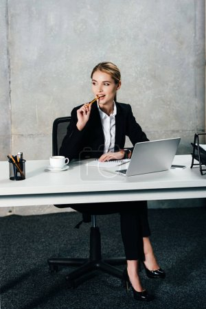 Photo for Young thoughtful businesswoman sitting at workplace and touching lips with pencil - Royalty Free Image