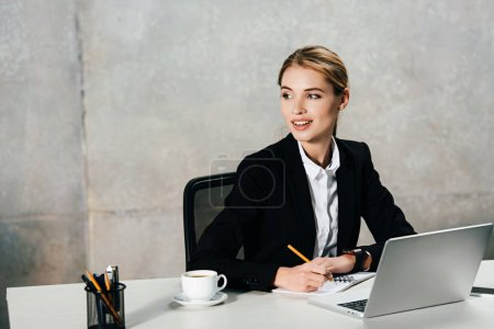 Photo for Smiling businesswoman sitting at workplace and writing in notebook - Royalty Free Image