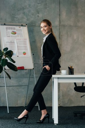 Photo for Smiling businesswoman standing by work desk and keeping hands in pockets - Royalty Free Image