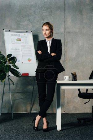 Photo pour Sérieux jeune femme d'affaires permanent de bureau avec bras croisés - image libre de droit