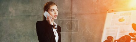 Photo for Beautiful concentrated businesswoman talking on smartphone in office - Royalty Free Image