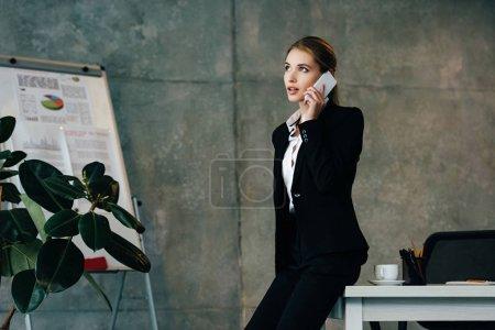 Photo pour Jeune femme d'affaires se tient debout sur le lieu de travail et parler sur smartphone - image libre de droit