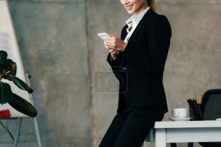 Photo for Cropped view of smiling pretty businesswoman using smartphone while standing by workplace - Royalty Free Image