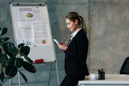 smiling businesswoman standing by work table and using smartphone