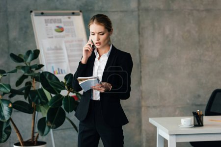 young serious businesswoman talking on smartphone and holding notebooks