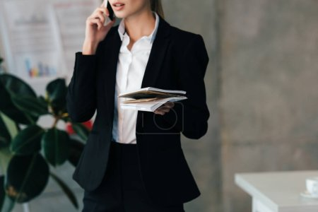 cropped view of businesswoman talking on smartphone and holding documents