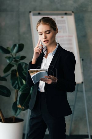 Photo for Young businesswoman seriously talking on smartphone while holding notebooks in hands - Royalty Free Image