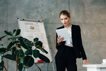 Photo pour Jeune femme d'affaires utilisant une tablette numérique tout en étant debout par le lieu de travail - image libre de droit