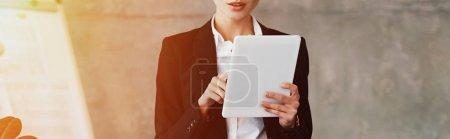 Photo pour Recadrée vue de la jeune femme d'affaires à l'aide de tablette numérique au bureau - image libre de droit