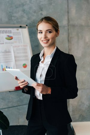 Photo for Beautiful smiling businesswoman holding digital tablet and looking at camera in office - Royalty Free Image