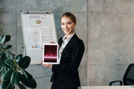 Photo for Smiling pretty businesswoman holding digital tablet with charts and graphs on screen - Royalty Free Image