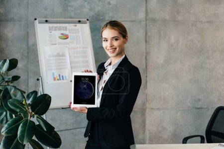 Photo for Beautiful smiling businesswoman showing ipad screen and looking at camera in office - Royalty Free Image