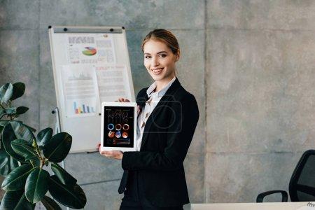 Photo pour Femme souriante tenant une tablette numérique avec les diagrammes sur écran - image libre de droit