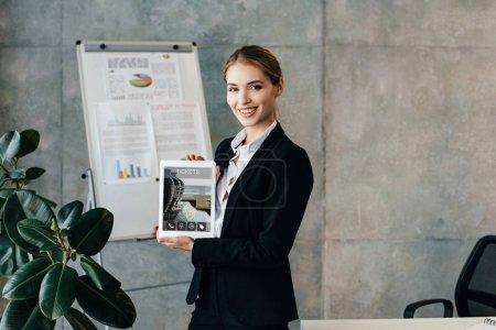 Photo pour Belle femme d'affaires souriante tenant une tablette numérique avec des billets à l'écran - image libre de droit