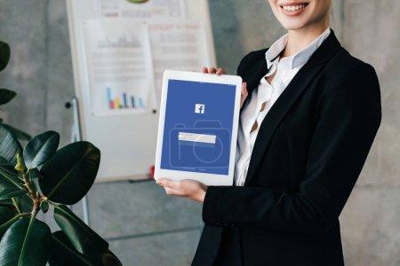 Foto de Vista parcial de empresaria muy sonriente con tableta digital con facebook en la pantalla - Imagen libre de derechos