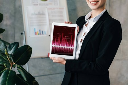 Photo for Partial view of smiling businesswoman holding digital tablet with charts on screen - Royalty Free Image