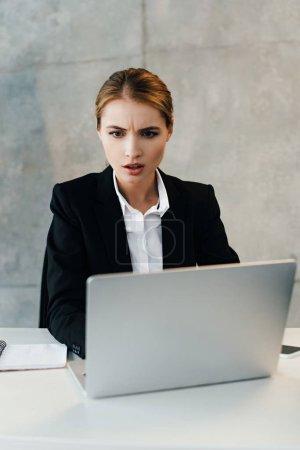 Photo pour Femme d'affaires choquée en utilisant un ordinateur portable au bureau - image libre de droit