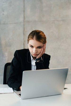 Photo pour Femme d'affaires concentré grave utilisant l'ordinateur portable tout en mettant heand sur place - image libre de droit