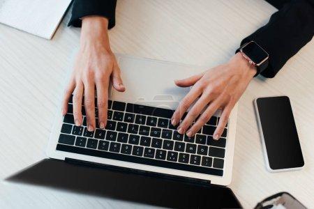 Photo pour Vue recadrée de jeune femme d'affaires à l'aide d'un ordinateur portable - image libre de droit