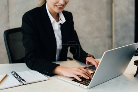Photo for Cropped view of smiling businesswoman using laptop in office - Royalty Free Image