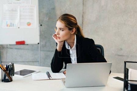 Photo pour Belle femme d'affaires pensif assis au milieu de travail et étaiement de tête avec la main - image libre de droit