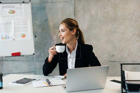 Photo pour Belle femme d'affaires riante assise au travail et buvant du café - image libre de droit