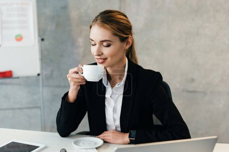 Photo for Attractive businesswoman enjoys drinking coffee with closed eyes while sitting at workplace - Royalty Free Image