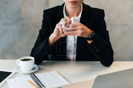 abgeschnittene Ansicht einer Geschäftsfrau am Arbeitsplatz mit zerknittertem Papier in den Händen