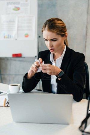 Photo pour Concentration sélective de la femme d'affaires stressée avec du papier froissé dans les mains - image libre de droit