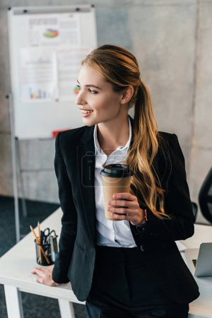 Photo for Selective focus of smiling businesswoman staying by work desk with disposal cup of coffee - Royalty Free Image