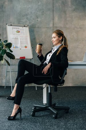 smiling businesswoman sitting on chair with paper cup of coffee