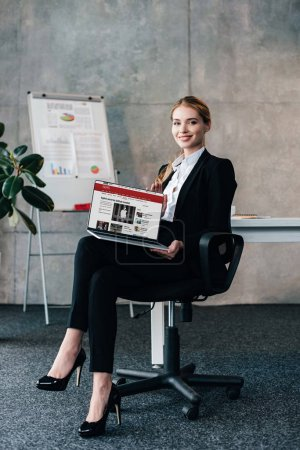 Photo for Attractive smiling businesswoman sitting on chair and holding laptop with bbc news on display - Royalty Free Image