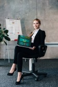 Businesswoman sitting in chair and holding laptop with football matches scores on screen