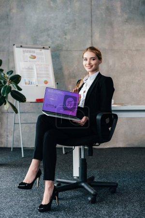 Photo pour Sourire de jolie femme d'affaires assis sur la chaise et tenant portable avec shopping site sur écran - image libre de droit