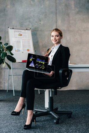 Photo pour Femme d'affaires souriante assise sur une chaise et tenant un ordinateur portable avec des diagrammes commerciaux à l'écran - image libre de droit