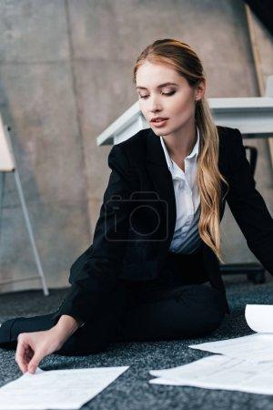 Photo pour Femme d'affaires en costume noir, assis sur le plancher et en tenant le document - image libre de droit