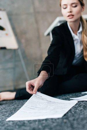 Foto de Vista recortada de la bella empresaria sentado en suelo y lectura de documentos - Imagen libre de derechos