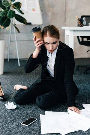 Photo pour Femme d'affaires épuisé, assis sur le plancher près de table de travail avec maux de tête - image libre de droit
