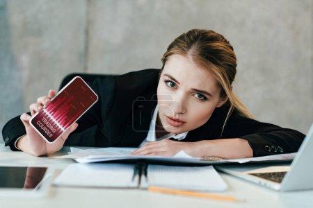 Photo pour Mise au point sélective de femme d'affaires à la table de travail affichage écran de smartphone avec cours trading - image libre de droit