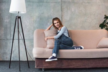 Photo for Young beautiful girl smiling, hugging pillow and sitting on pink sofa in room - Royalty Free Image